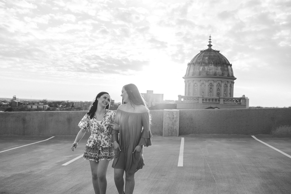 Black and white image of best friends holding on to one another and walking on a rooftop in downtown OKC by Amanda Lynn.