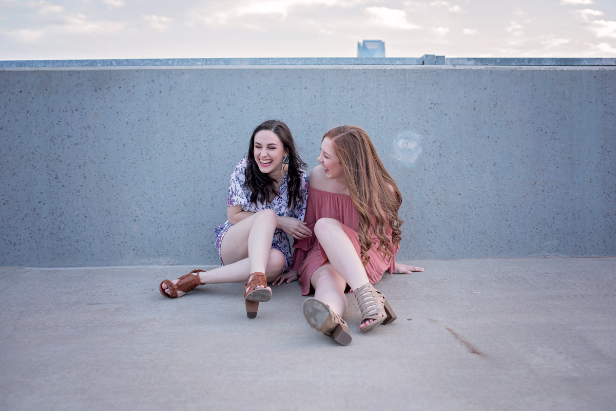 High School senior girls sitting on rooftop of parking garage talking and laughing in Oklahoma City.