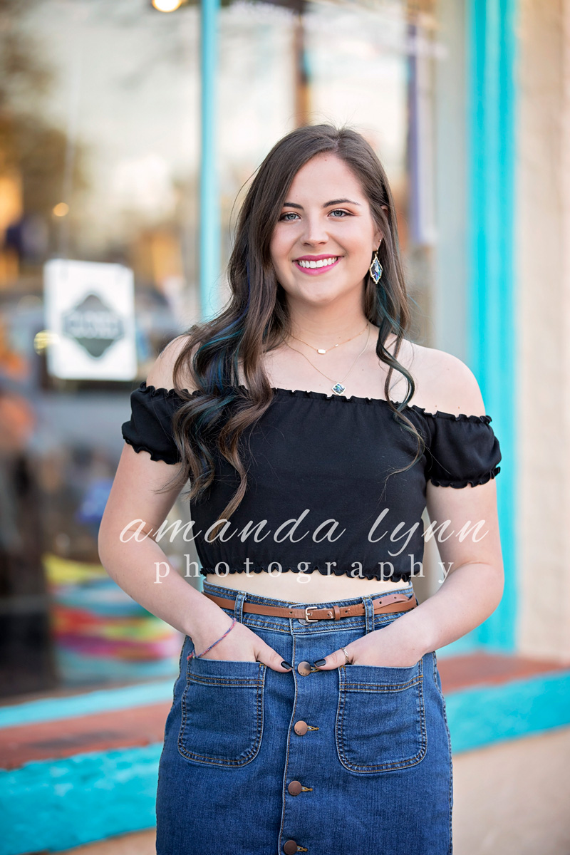 Senior girl wearing black top with jean skirt, standing with hands in pockets in the Paseo District in Oklahoma City.