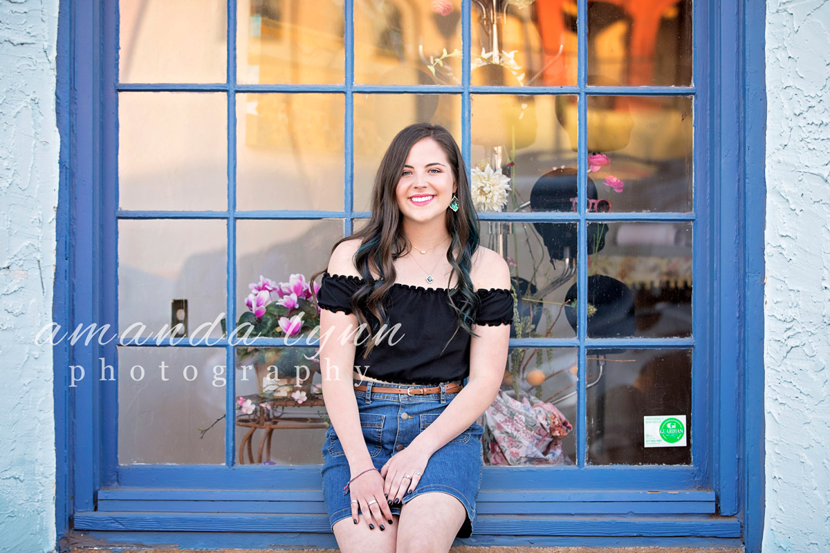 High School senior girl wearing black top and jean skirt, sitting in blue window in the Paseo District in Oklahoma City, by Amanda Lynn Photography.