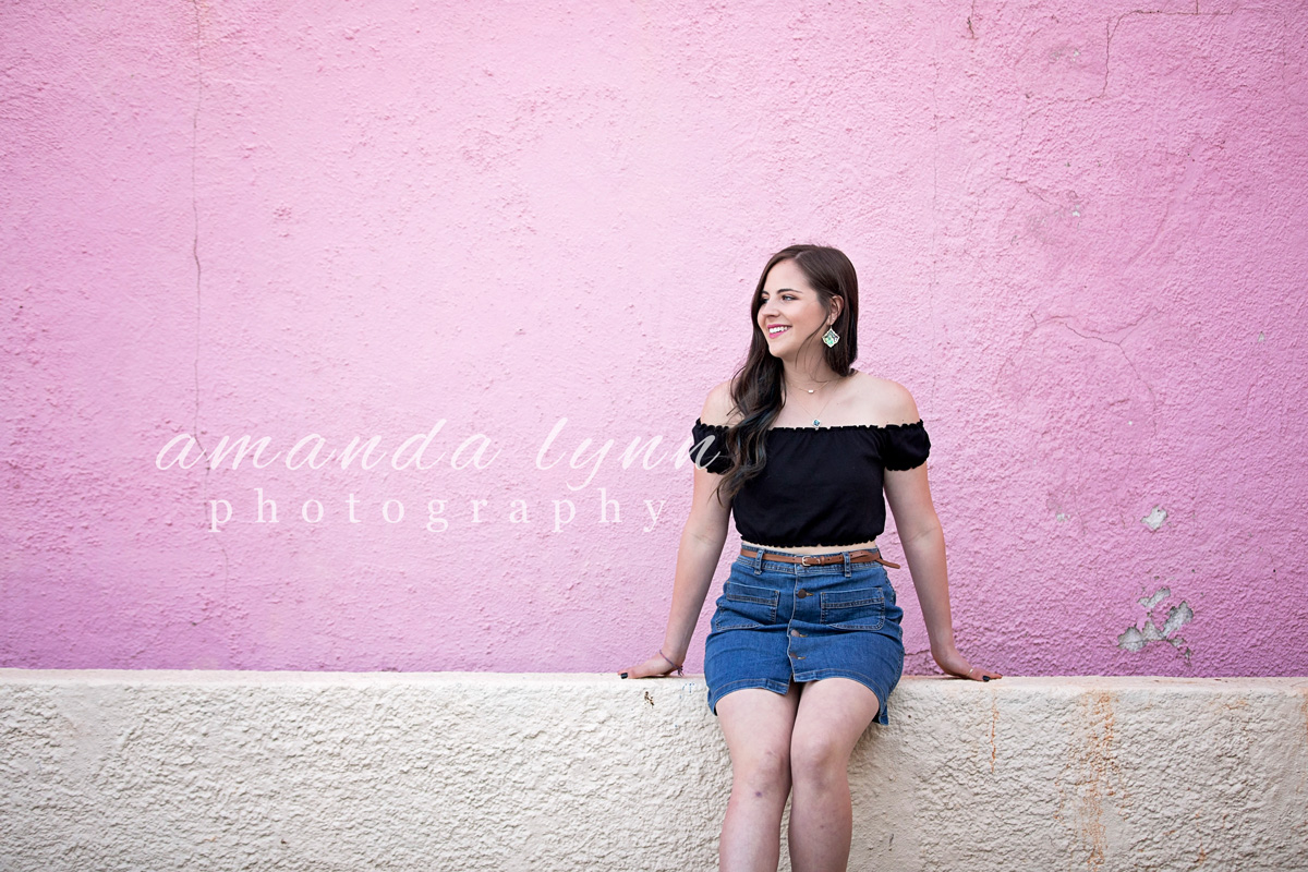 Senior girl wearing black top and jean skirt, leaning against pink and white wall in the Paseo District in Oklahoma City by Amanda Lynn.