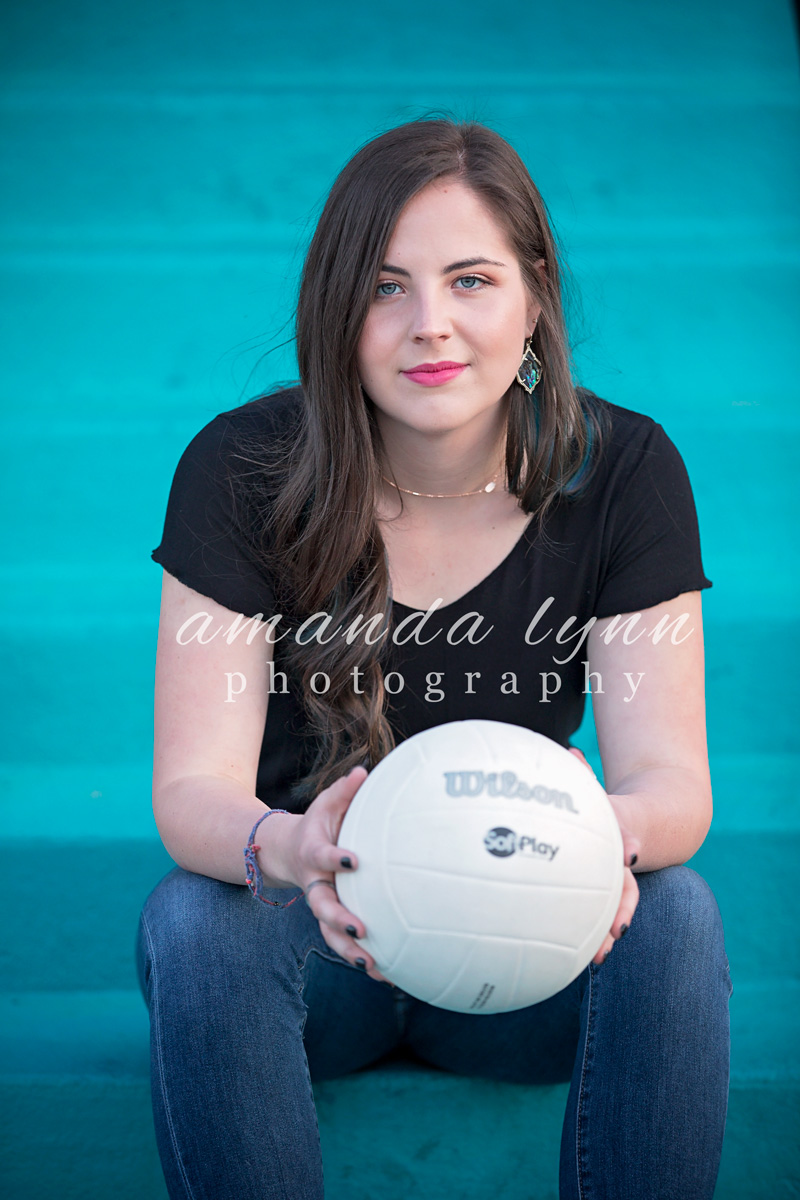 Senior girl with long brown hair, sitting on blue steps holding a white volleyball in the Paseo District in Oklahoma City, by Amanda Lynn Photography.