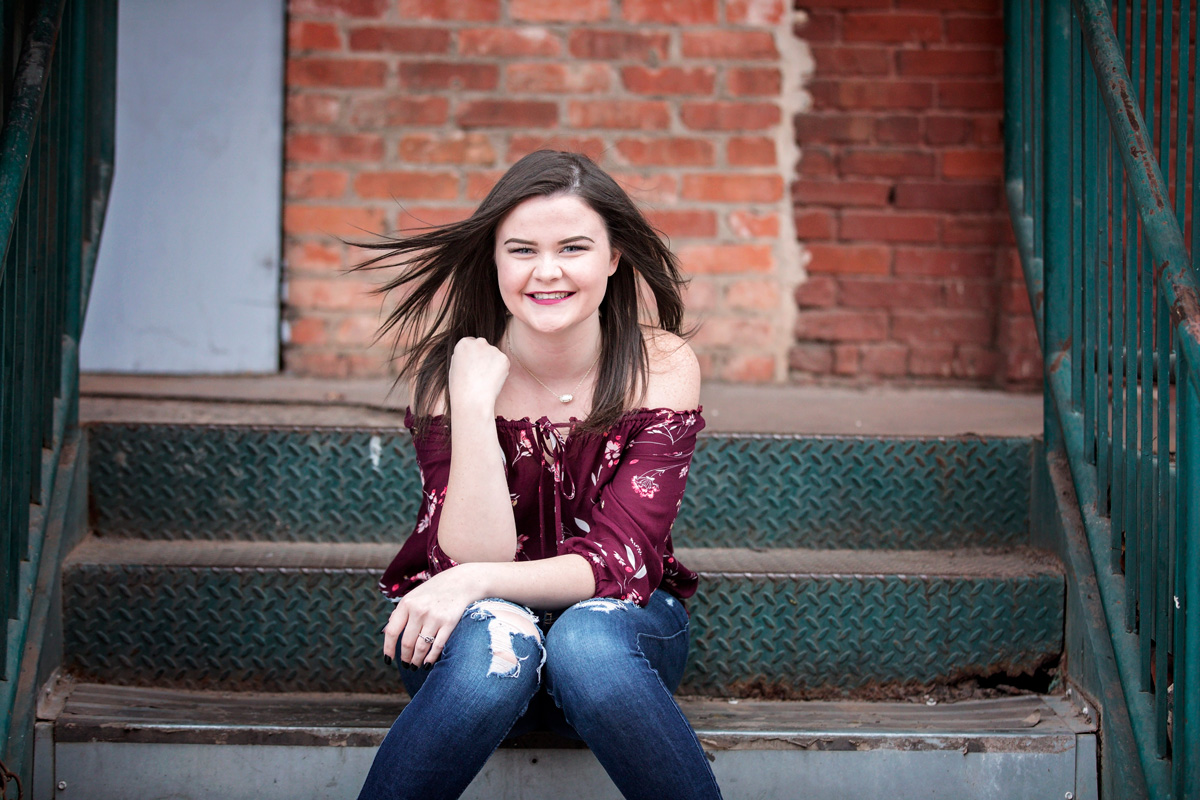 High school senior girl wearing maroon top, sitting on greet stairs looking at camera in downtown Oklahoma City.