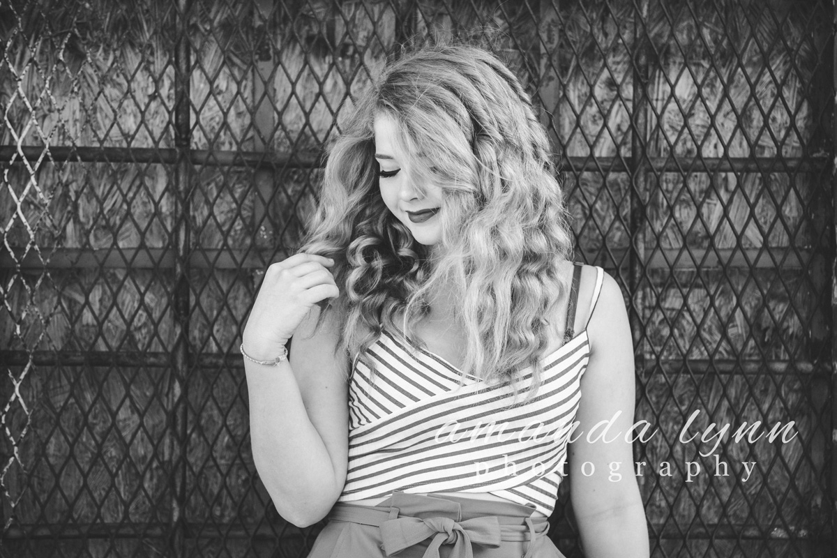 Black and white image of high school senior girl holding long curly hair and looking down at her shoulder in Oklahoma City, Oklahoma.
