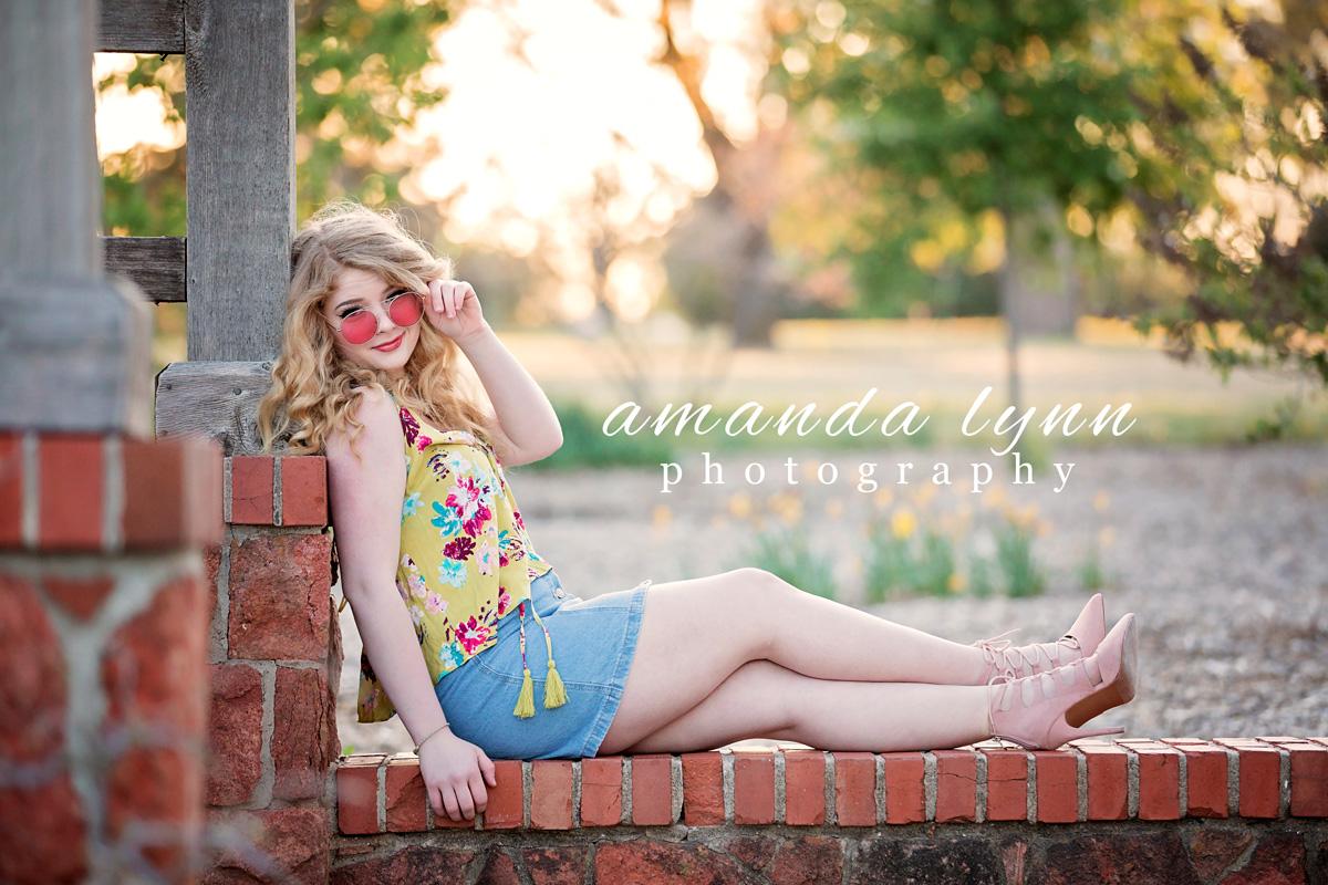 Senior girl wearing yellow summer top and jean skirt, sitting on bricks at will rogers park in Oklahoma City, Oklahoma by Amanda Lynn.