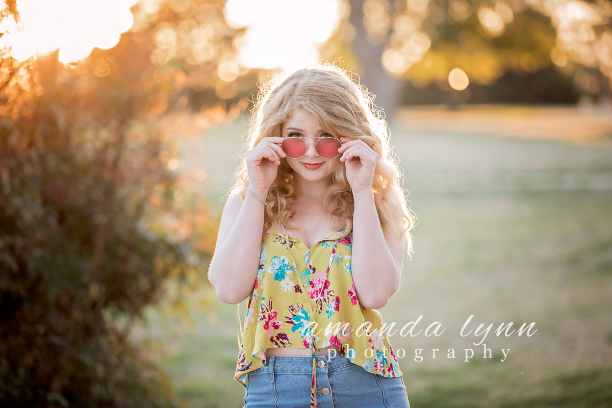 Senior girl with long, blonde hair, wearing yellow summer shirt, looking over the top of her sun glasses while standing in Will Rogers Park in Oklahoma City.