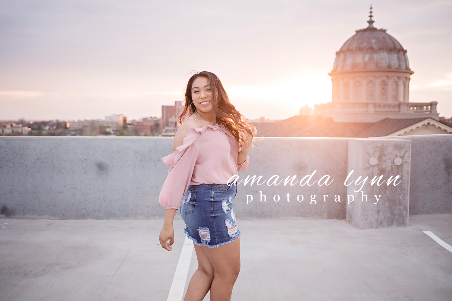 Oklahoma city senior girl wearing pink top and jean skirt, dancing on top of parking garage in Oklahoma City, Oklahoma by Amanda Lynn.