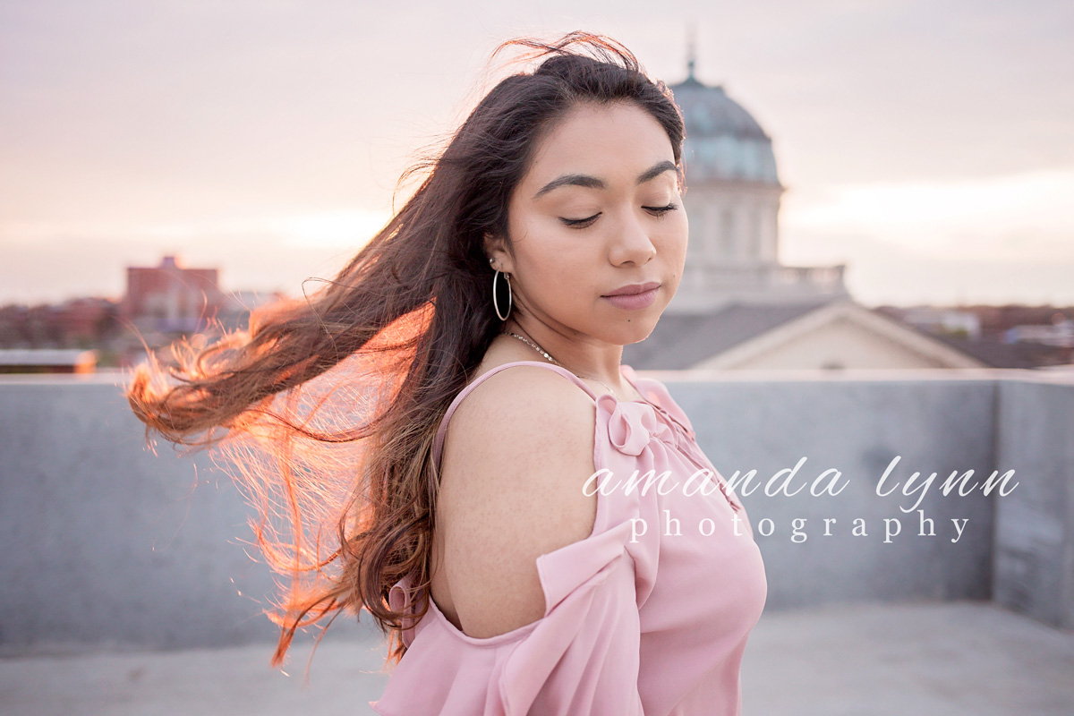 Senior girl with long brown hair backlit from the sun on top of parking garage in Oklahoma City, by Amanda Lynn Photography.