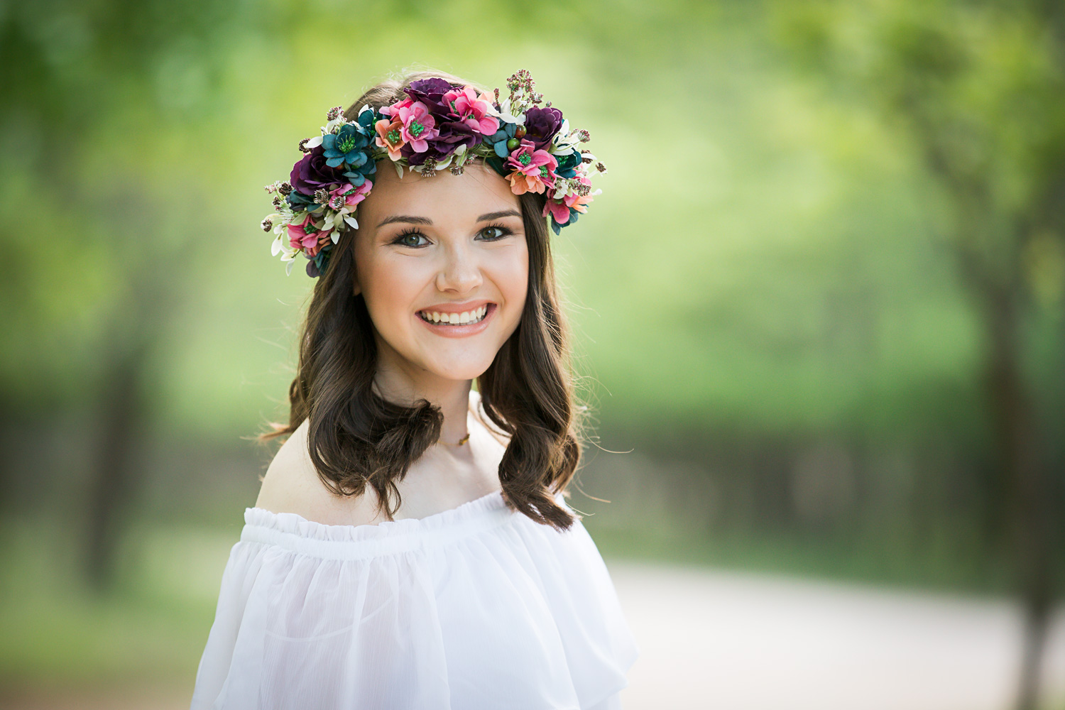 High school senior girl wearing white top and flower crown, looking and smiling at camera.