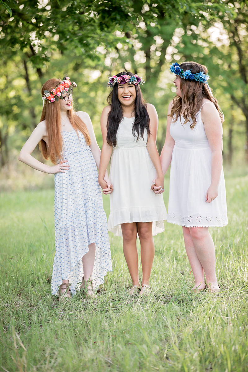 Three senior girls holding hands and laughing at Martin Nature Park in Oklahoma City.