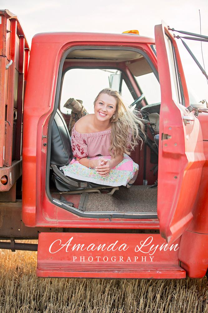 High School senior girl laying in old orange truck in a wheat field by Amanda Lynn.