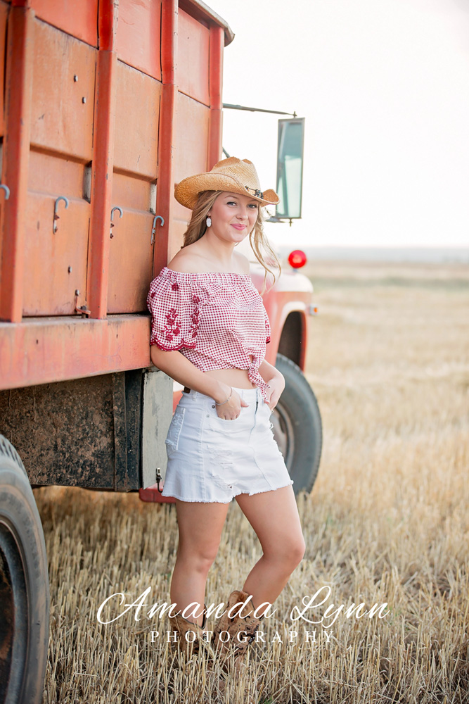 Senior girl wearing white jean skirt and cowboy hat, leaning against old truck in a wheat field in western Oklahoma.
