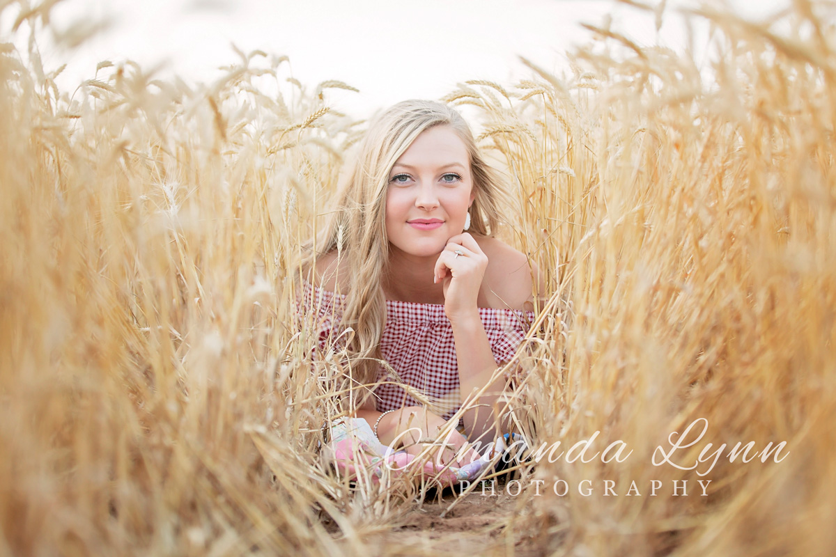 Senior girl with long blonde hair laying on stomach in wheat field in western Oklahoma by Amanda Lynn Photography.