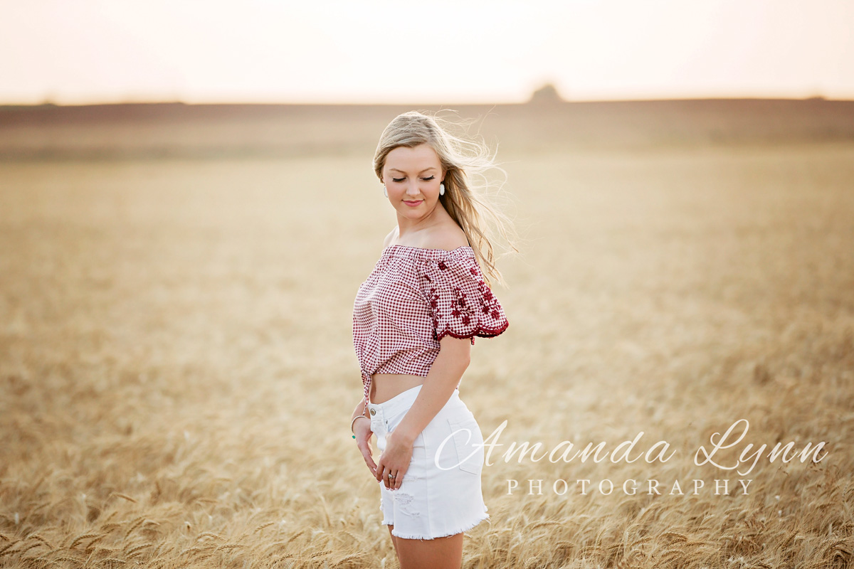Senior girl wearing red top and white skirt, standing in wheat field and looking over shoulder in western Oklahoma.