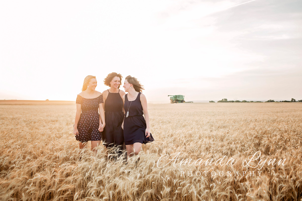 Mother and daughters wearing blue dresses and cowboy boots, walking through a wheat field in western Oklahoma by Amanda Lynn Photography.