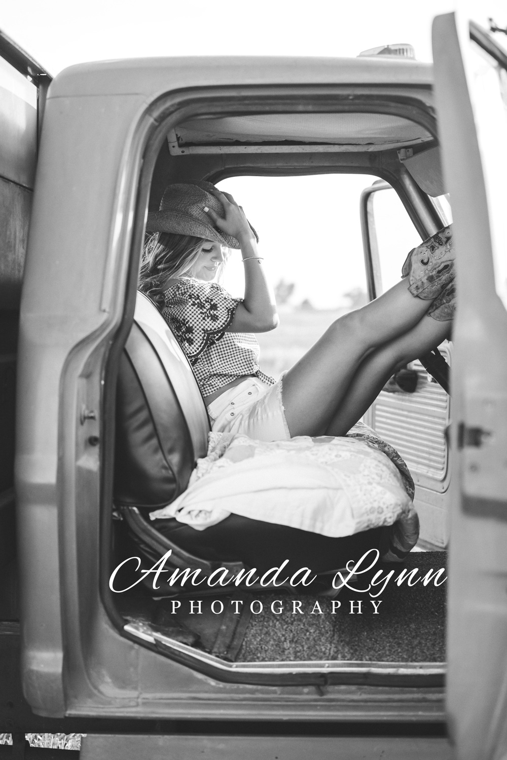 Black and white image of senior girl sitting in an old truck in Oklahoma.