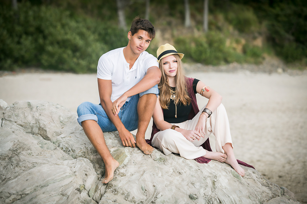 High school senior sweethearts, sitting on giant rock on the Oregon Coast by Amanda Lynn.
