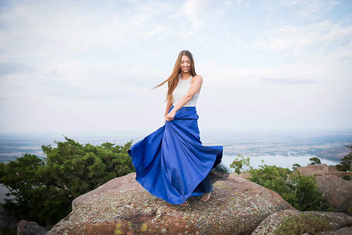 High school senior girl wearing blue prom dress, dancing on top of Mount Scott in Oklahoma by Amanda Lynn Photography.