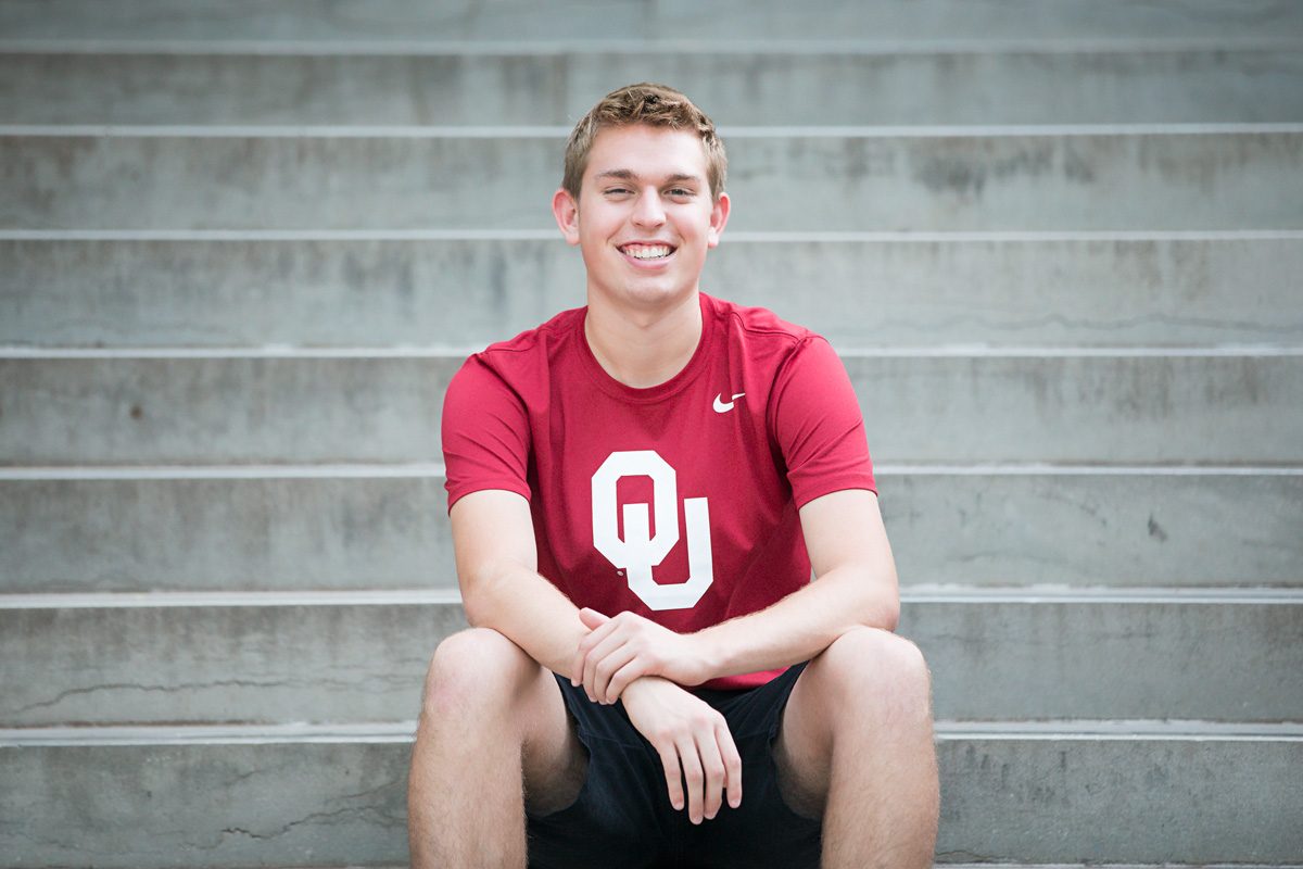High School senior boy wearing red OU t-shirt, sitting on steps at the OU campus by Amanda Lynn.
