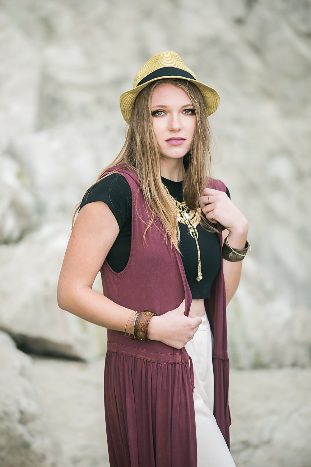 High School senior girl with long dirty blonde hair, wearing a hat, looking directly at camera by Amanda Lynn Photography.