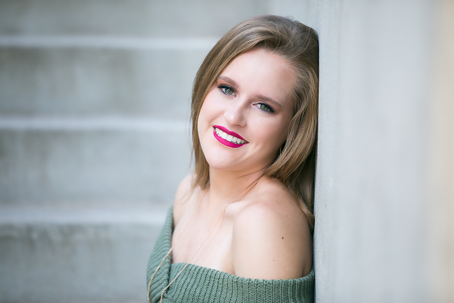 Senior girl wearing green sweater, leaning against concrete wall in downtown Oklahoma City by Amanda Lynn.