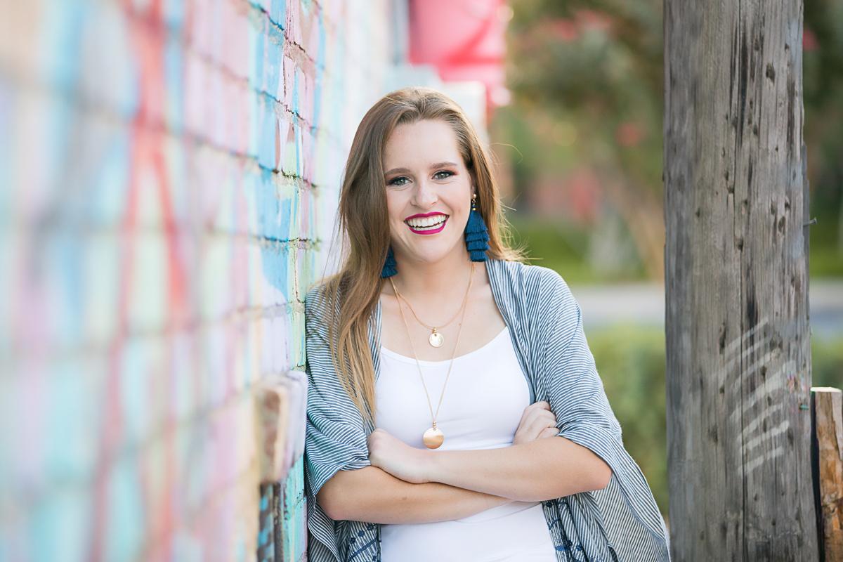 Senior girl with long blonde hair, leaning against graffiti wall, smiling at camera in downtown Oklahoma City by Amanda Lynn.