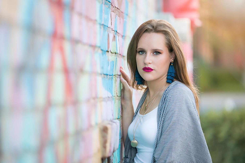 Senior girl wearing long blue earrings, leaning against graffiti wall in downtown Oklahoma City.