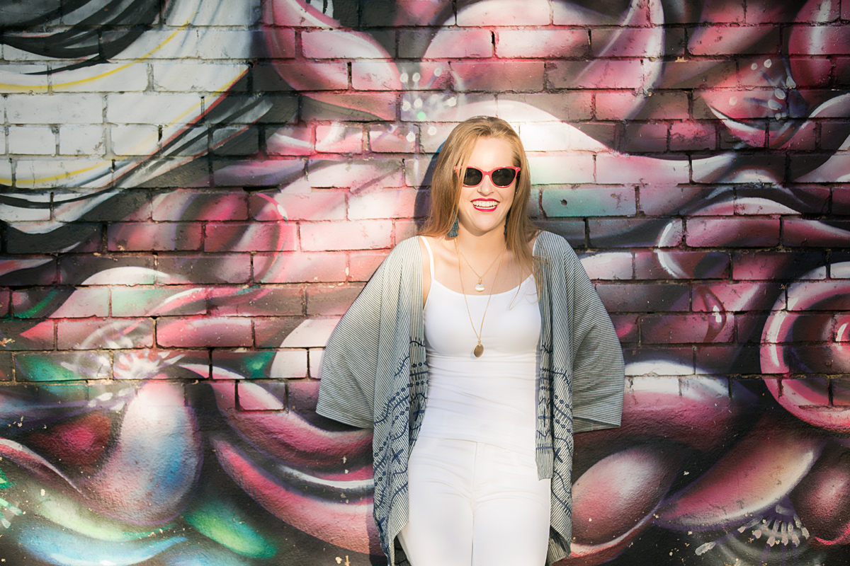 Senior wearing sunglasses, leaning against graffiti wall in downtown Oklahoma City.