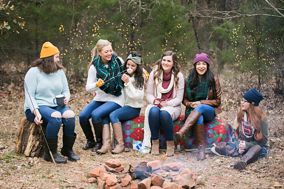 Group of high school senior girls wearing fall colors, sitting around a camp fire in the woods in Oklahoma City, Oklahoma by Amanda Lynn.