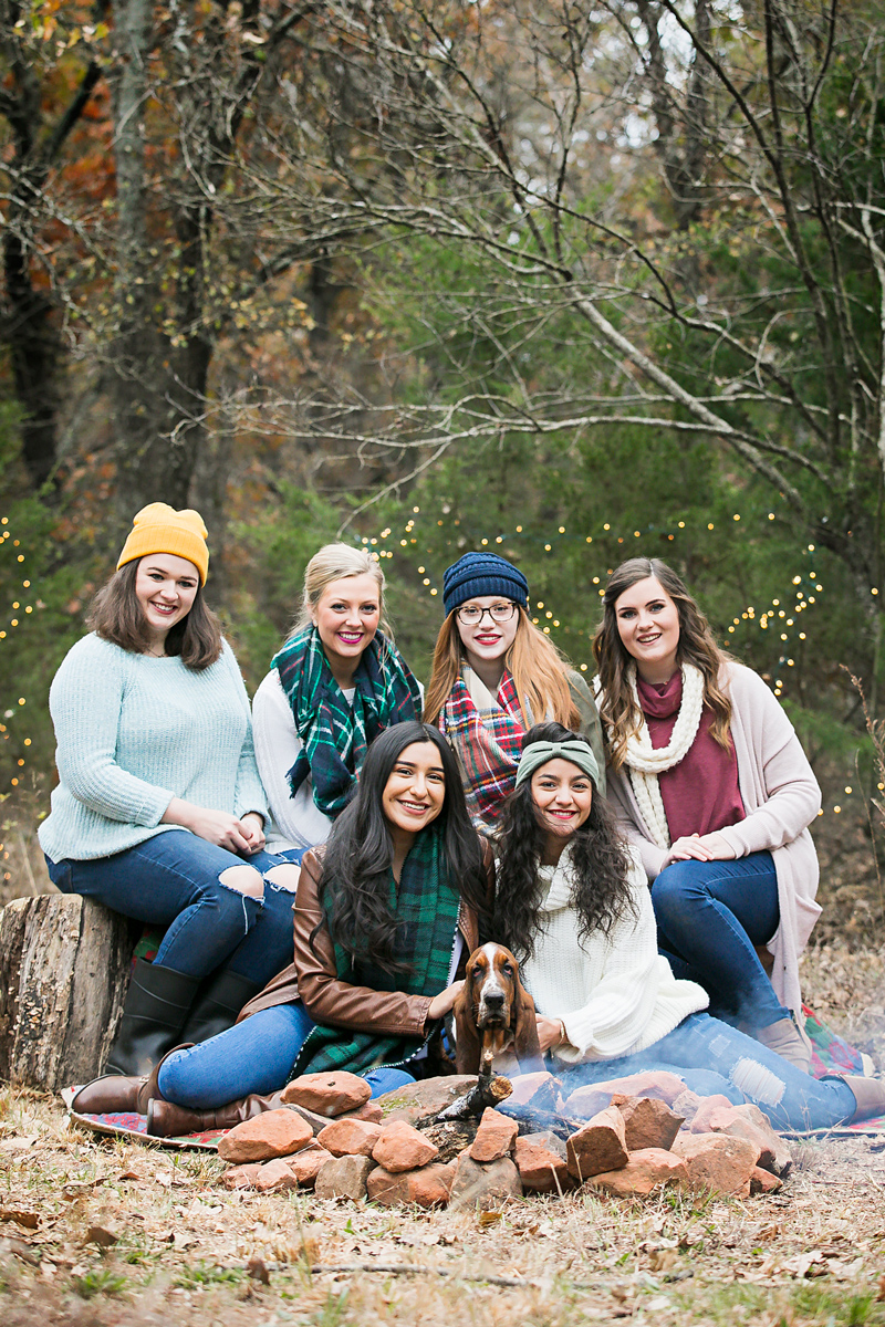 Amanda Lynn Photography senior elite team sitting around a camp fire in the woods with a basset hound puppy in Oklahoma.
