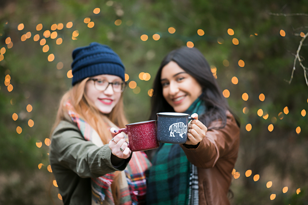 Two senior girls holding up coffee mugs in the woods in Oklahoma City by Amanda Lynn.