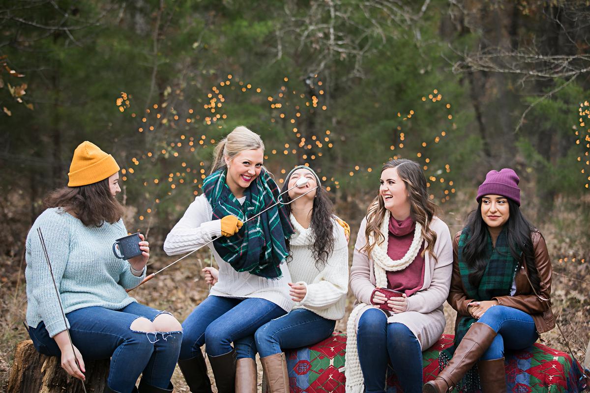 Amanda Lynn Photography elite senior team sitting around a camp fire roasting marshmallows at a group shoot in Oklahoma City.