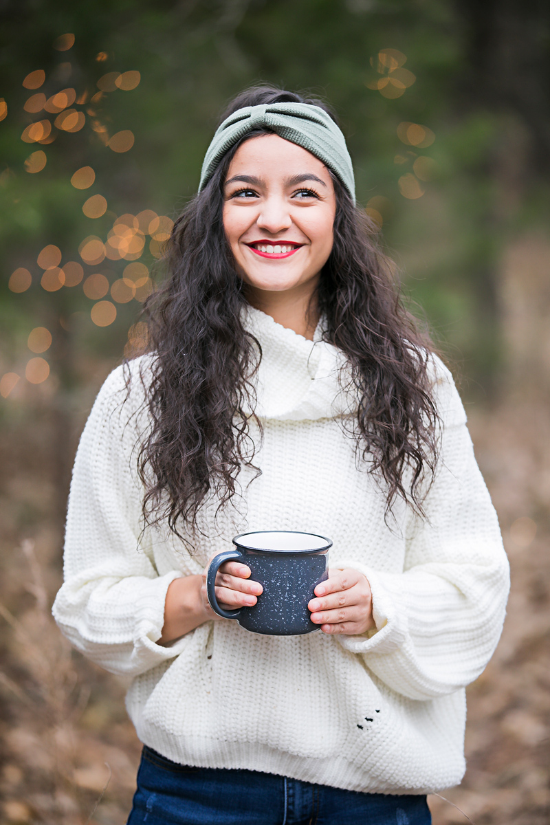 High school senior girl wearing a white sweater, holding a blue coffee mug, standing in the woods in Oklahoma by Amanda Lynn Photography.