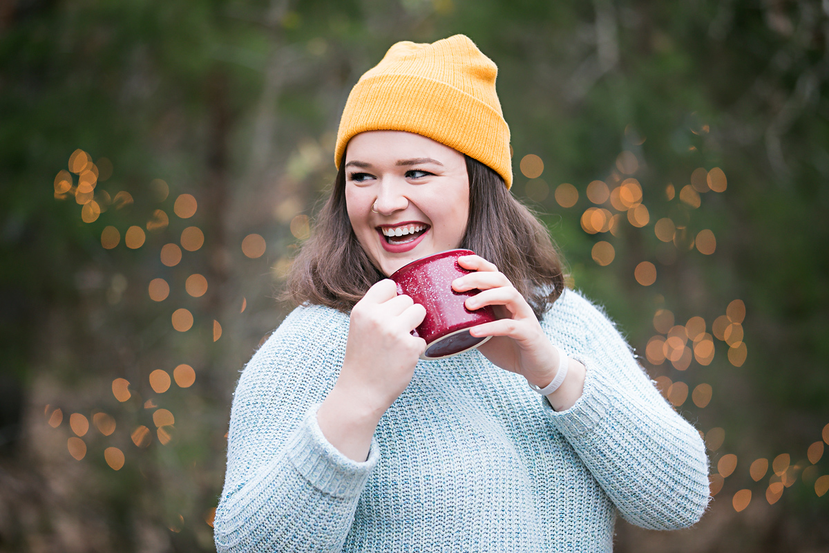 Senior girl wearing blue sweater and yellow hat, holding coffee mug and laughing by Amanda Lynn Photography.