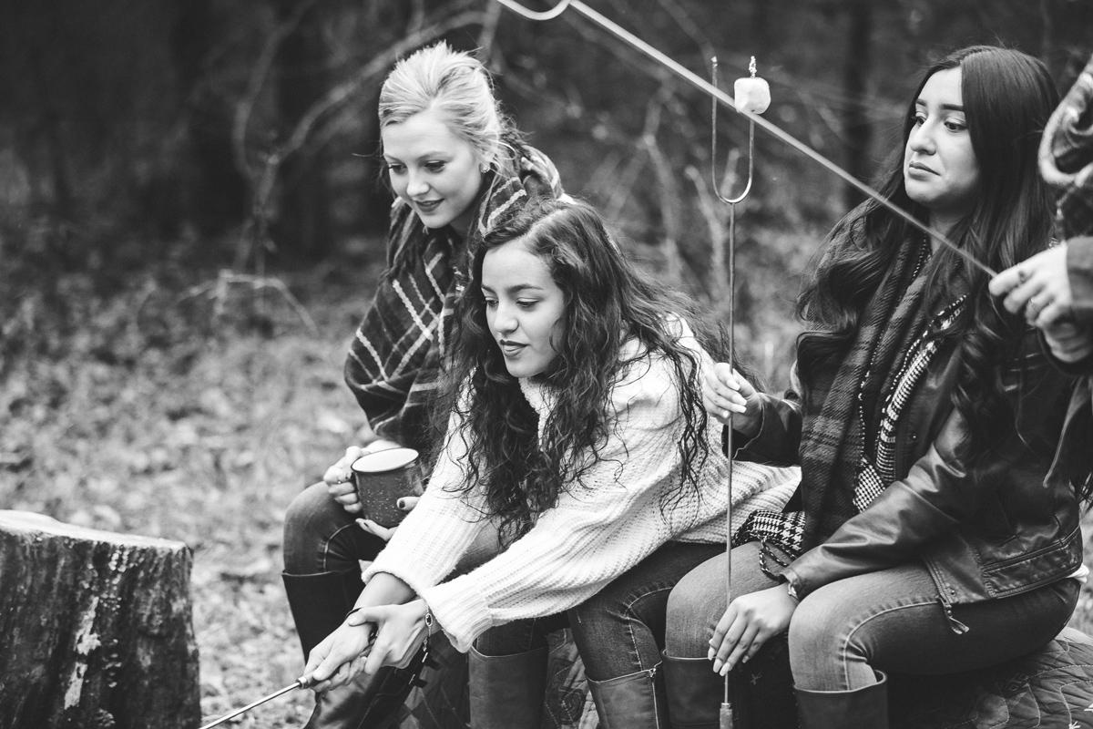 Black and white image of Oklahoma High School Seniors sitting around a camp fire by Amanda Lynn.