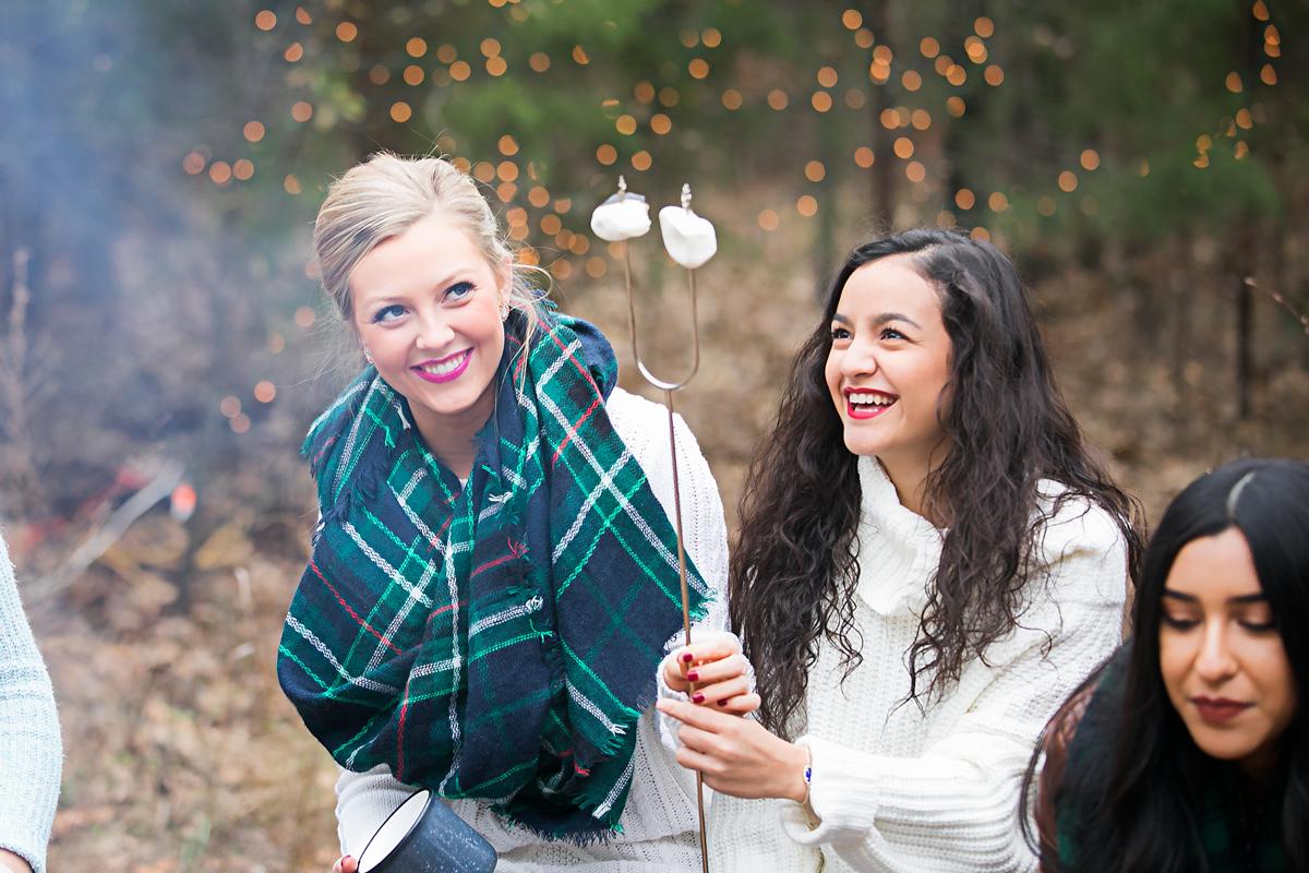 Oklahoma High School Seniors sitting around a camp fire, roasting marshmallows at group photoshoot by Amanda Lynn Photography.