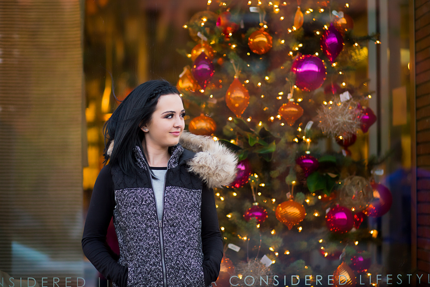 High school senior girl wearing black coat standing in front of a window with a christmas tree in Automobile Alley in Oklahoma City.
