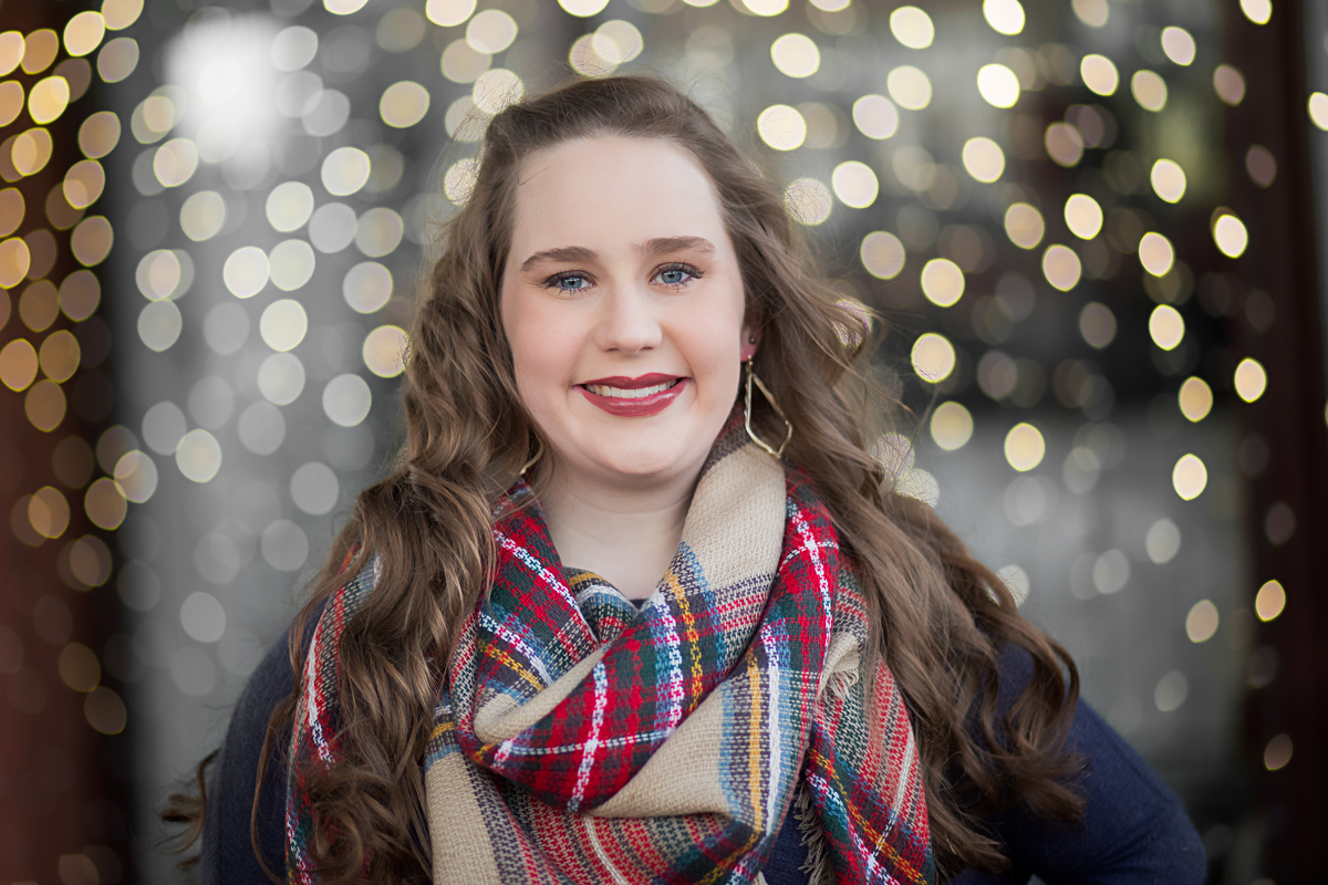 Senior girl standing in front of white christmas lights in automobile alley in Oklahoma City by Amanda Lynn.