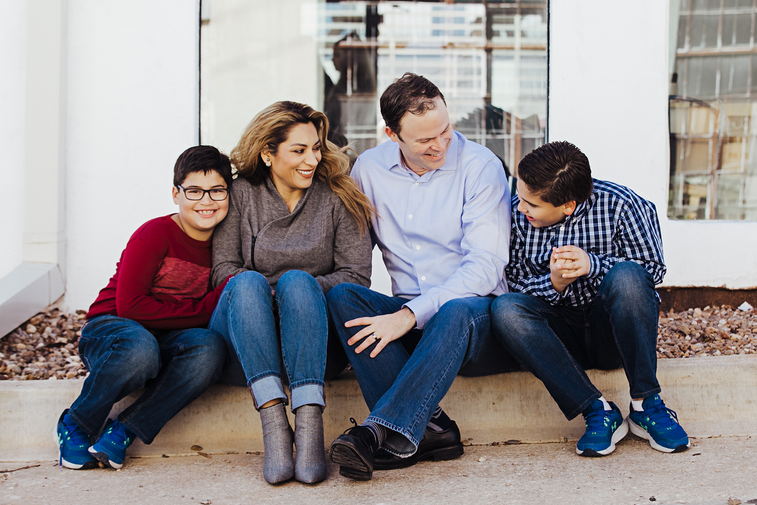 Family of four sitting on curb in Paseo District by Amanda Lynn, Oklahoma Family Photographer.