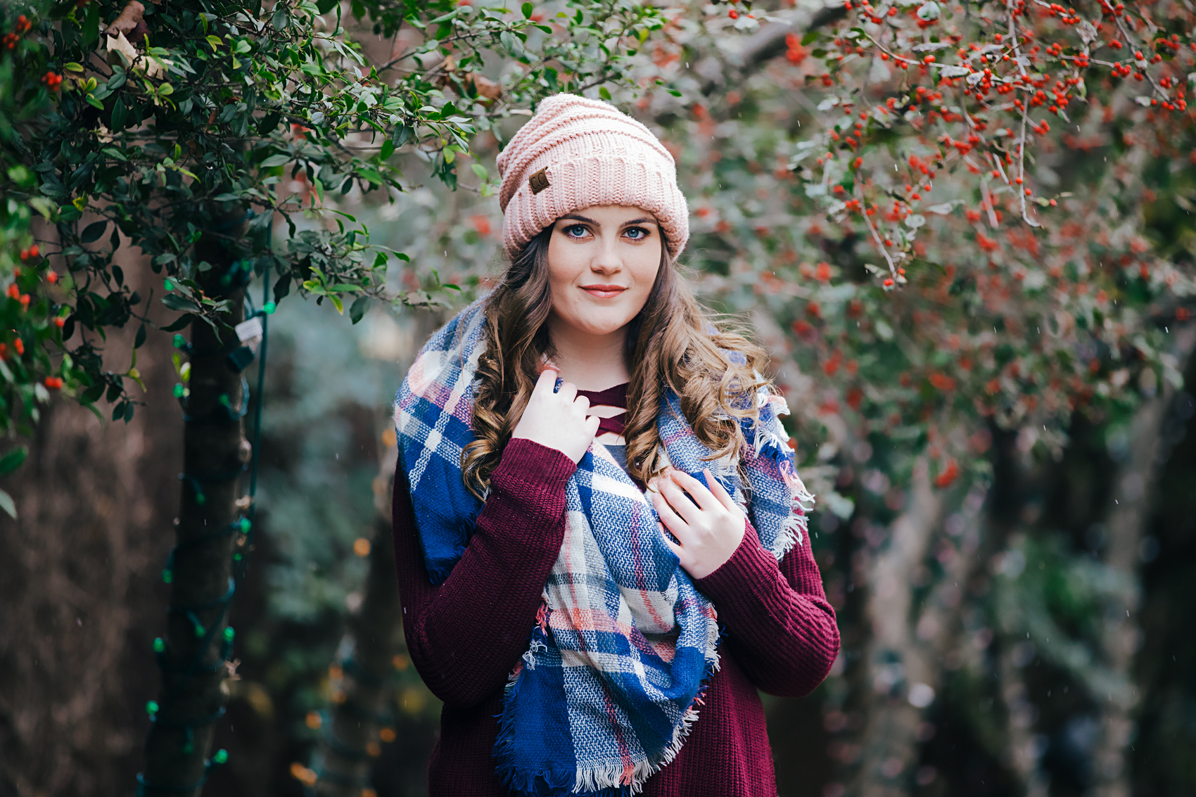 Senior girl wearing pink hat and blue scarf, standing in the snow in downtown Oklahoma City by Amanda Lynn Photography.