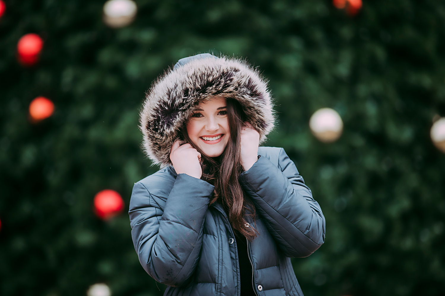 Oklahoma senior girl wearing coat with fuzzy hood, standing in front of Christmas tree in downtown Oklahoma City by Amanda Lynn Photography.
