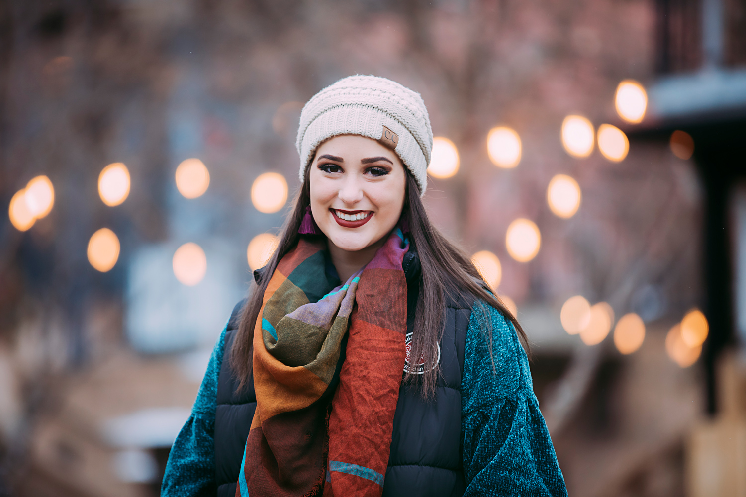 High school senior girl wearing tan hat standing in front of Christmas lights in downtown Oklahoma City by Amanda Lynn Photography.