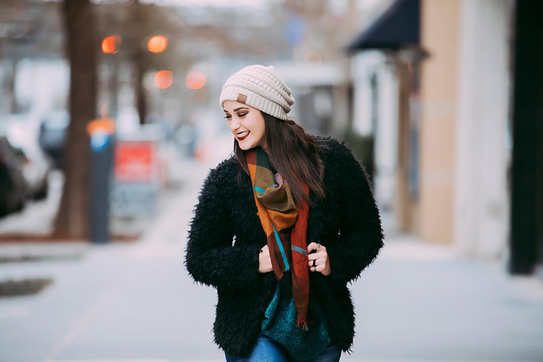 Senior girl wearing black coat and tan hat walking on sidewalk in downtown Oklahoma City by Amanda Lynn.