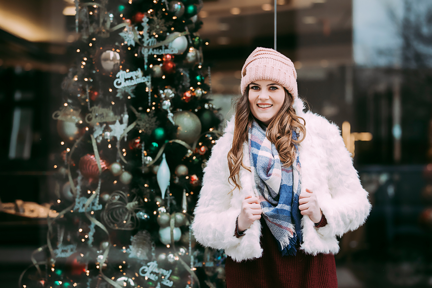 High school senior girl wearing white coat and pink hat standing in front of a christmas tree in downtown Oklahoma City by Amanda Lynn Photography.