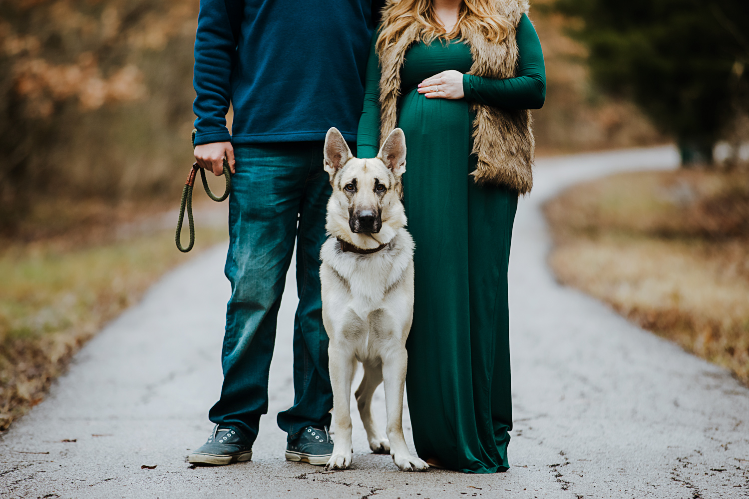 Couple wearing green and blue winter clothing, standing on trail with their German Shepard looking at camera in Oklahoma by Amanda Lynn Photography.