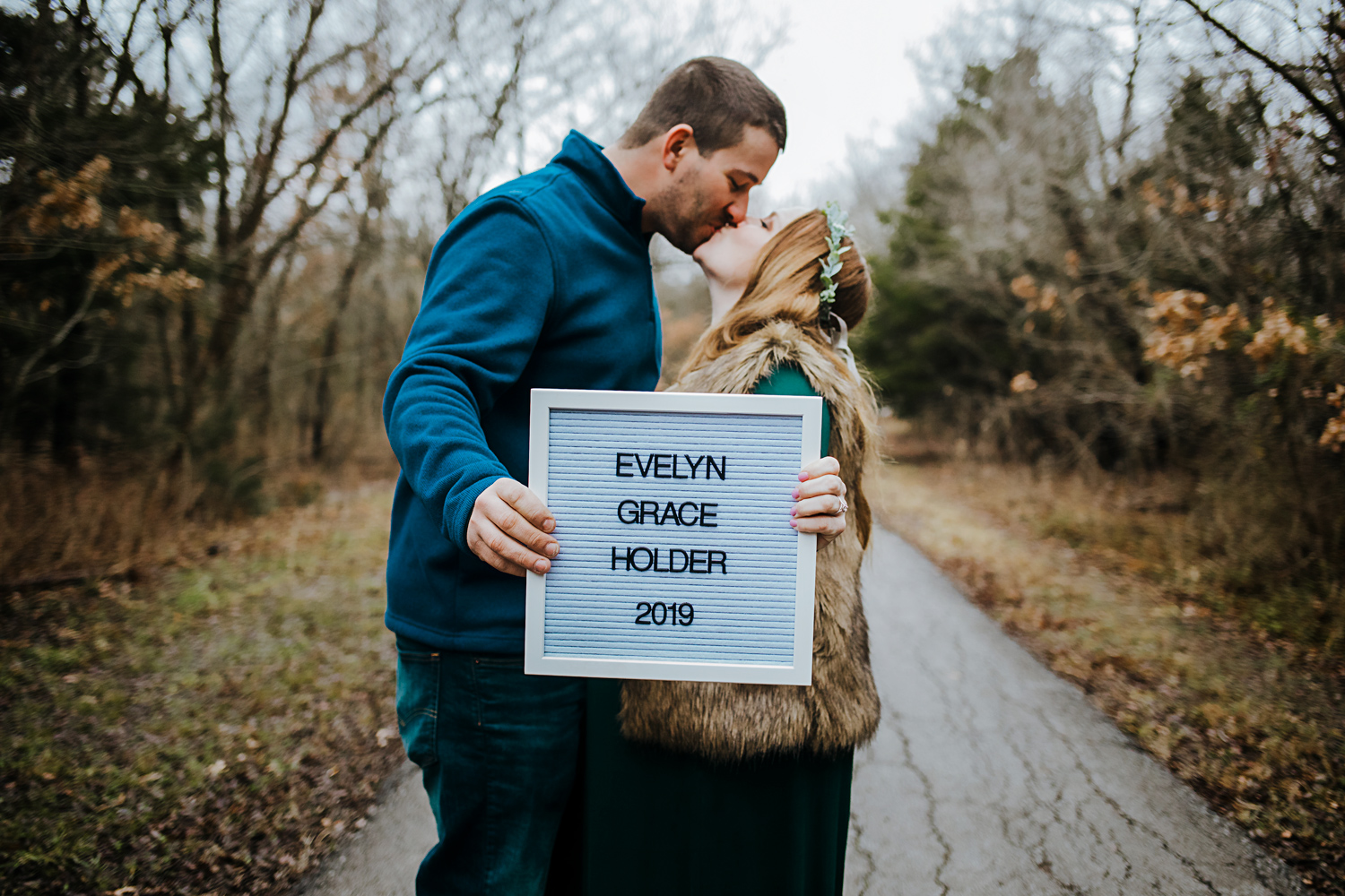 Couple kissing and holding sign that is announcing the name of their baby girl in Oklahoma by Amanda Lynn Photography.