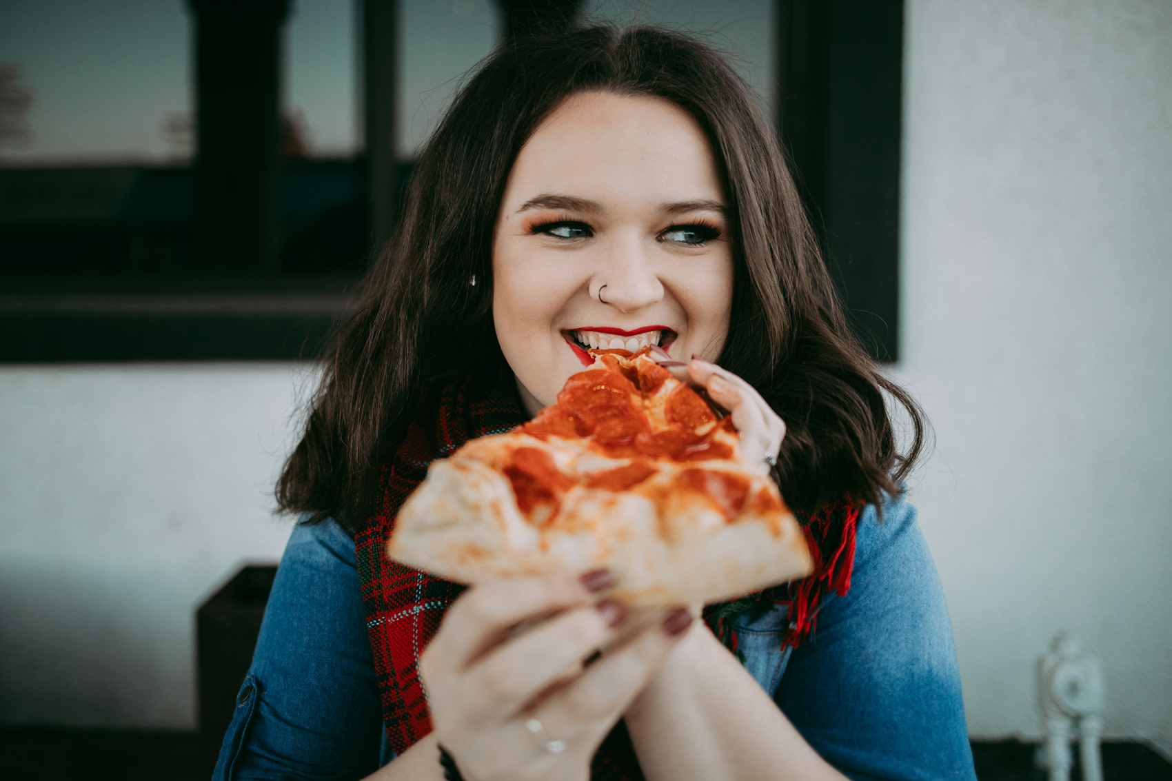 High school senior girl with long dark hair, eating a piece of pizza in the plaza district in Oklahoma City by Amanda Lynn Photography.