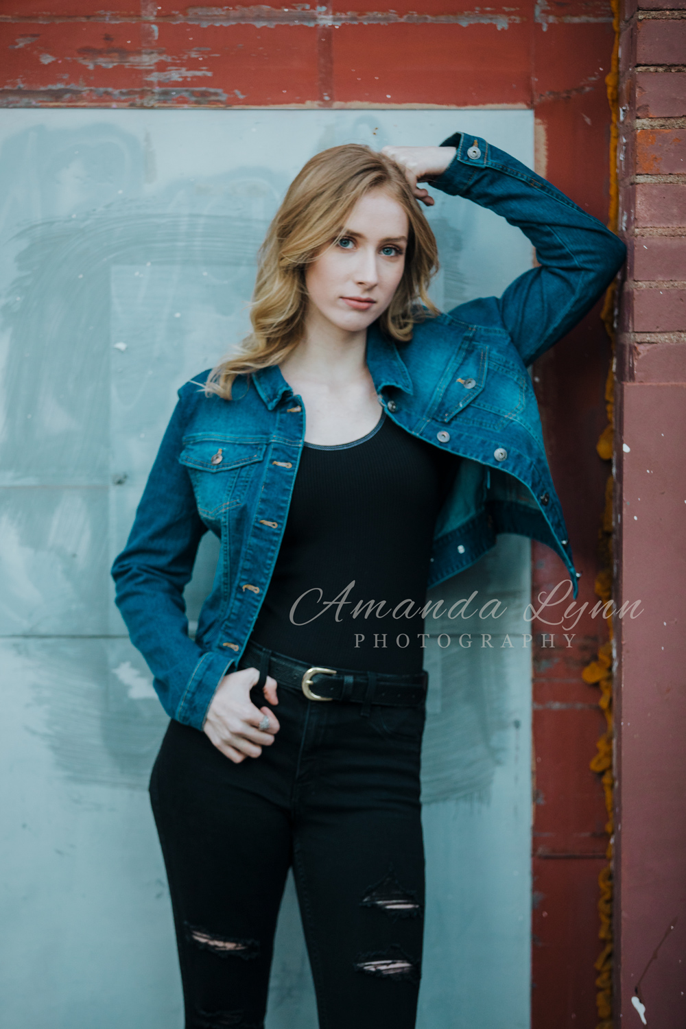 High school senior girl wearing black jeans with blue jean jacket, leaning agist a red wall in downtown Tulsa by Amanda Lynn.