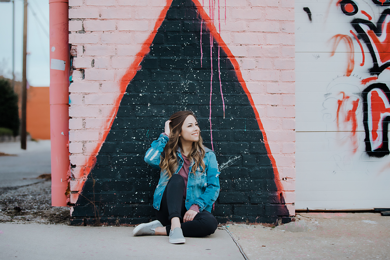 High school senior girl with long brown hair, wearing black pants and a jean jacket, sitting on concrete in from of a graffiti wall in Automobile Alley.