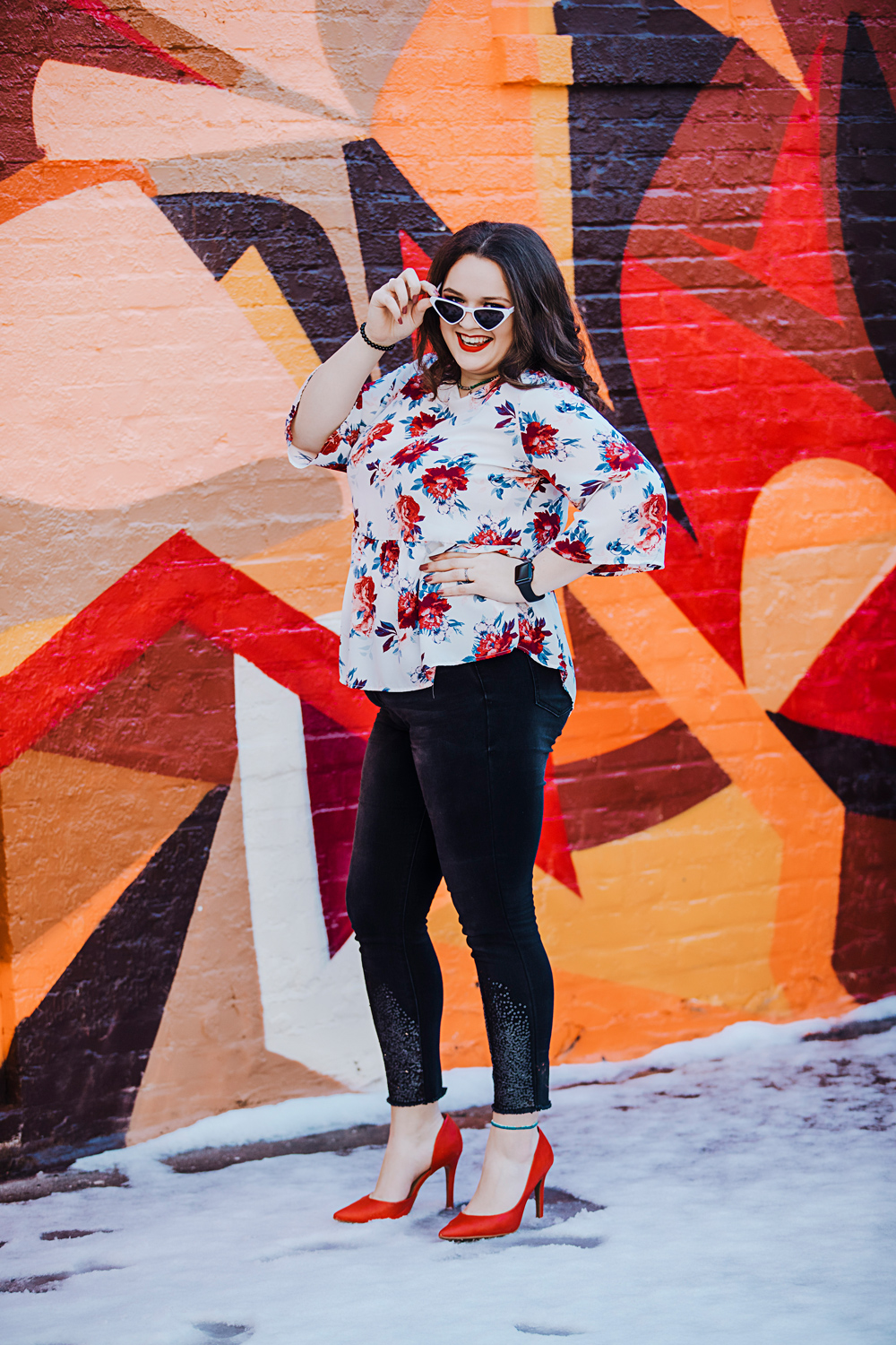 Oklahoma Senior girl wearing black pants, red heels, and a floral shirt standing in snow in front of a graffiti wall in the Plaza District in Oklahoma City.